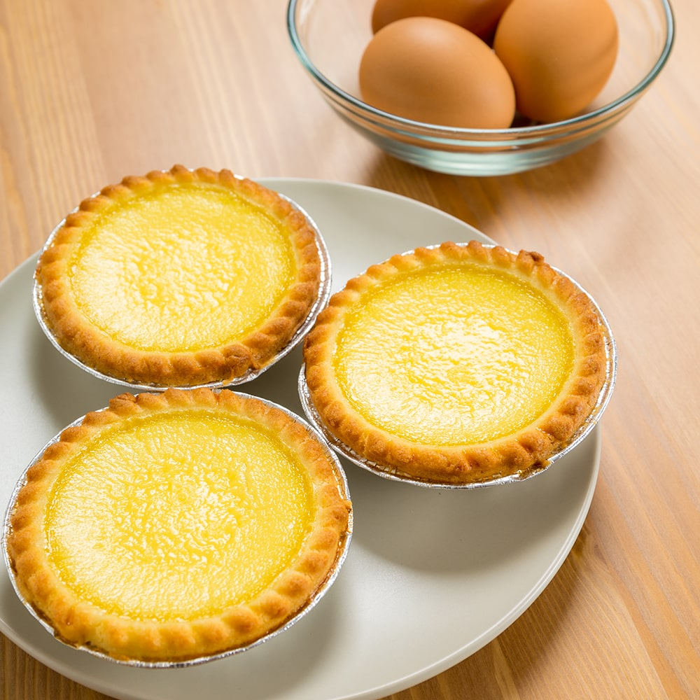 set of three egg tarts on a white plate with a bowl of eggs on a wooden table